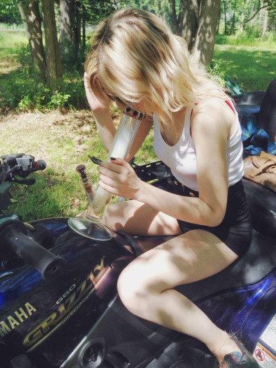 blonde girl in the park taking a bong hit
