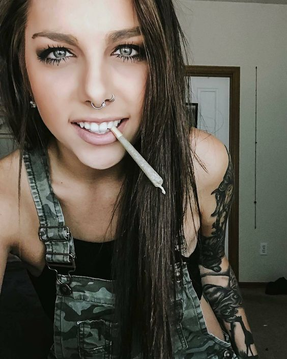 stoner girl in overalls with nose ring and joint